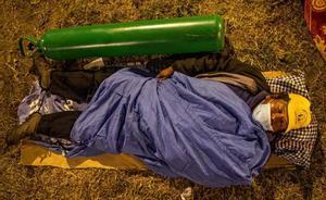 Perú revive el drama de la escasez de oxígeno en la segunda ola de la pandemia. En la foto, un ciudadano duerme toda la noche al raso para poder rellernar las botellas de oxígeno para sus familiares enfermos de covid en Callao (Perú).