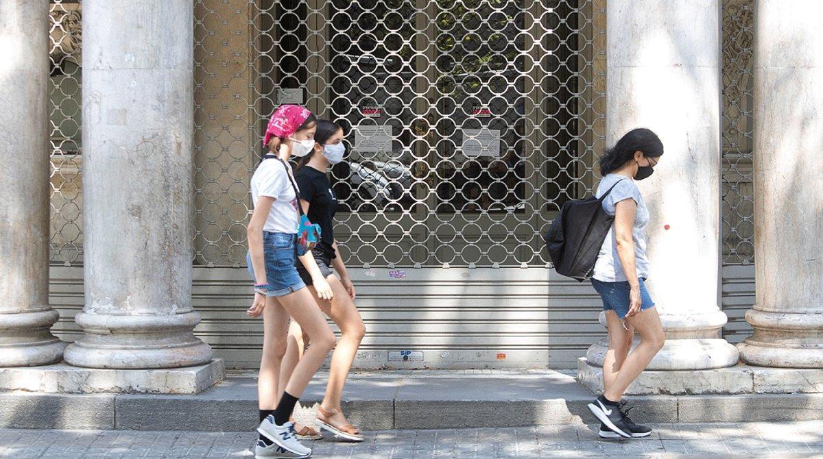 Un grupo de jóvenes pasan por delante del Teatre Coliseum de Barcelona, nuevamente cerrado por los rebrotes de coronavirus, el lunes 27 de julio.