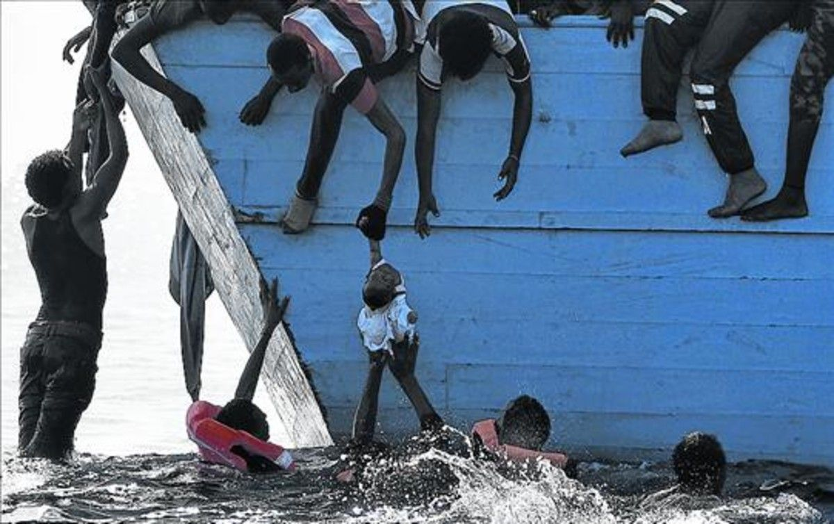 Unos inmigrantes tratan de sacar a un niño del mar frente a las costas de Libia, en una foto de archivo.