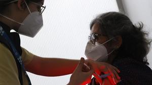 Una mujer del Servicio Gallego de Salud (Sergas) vacuna a las primeras personas de entre 50 y 55 con las dosis de AstraZeneca, este jueves.