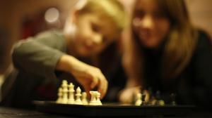 Un niño superdotado juega con su madre al ajedrez.