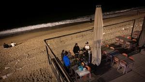 Barcelona 04/04/2021 Barcelona.Botellon i ambiente en la Barceloneta sobre las 21:00h.Grupo de jovenes bebiendo en unas mesas de una terraza de un restaurante cerrado por las restricciones. Barceloneta. AUTOR: Manu Mitru