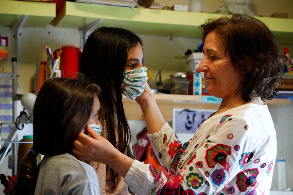 Una mujer prueba unas mascarillas a unas niñas, en Córdoba.