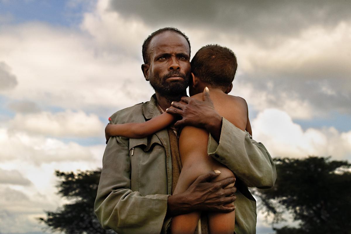 Era una emergencia nutricional en una zona de Etiopía donde la desnutrición ya es endémica. Lasequía y las plagas de langostas habían vuelto a dejar baldíos todos los terrenos de la región, y las cosechas habían dejado de serlo. Nollovía y, si lo hacía, quedaba todo anegado. Numerosas madres se arremolinaban a las puertas del centro nutricional, pero la imagen apareció de repente. Unpadre llevaba a su hijo en brazos. Mesorprendió. Noera lo habitual, aunque lo más llamativo era su mirada. Sellamaba Abebaye y el niño, Basada Moti. Volví a la región al cabo de un tiempo y los visité en su aldea. (Oromía, Etiopía, 2008).