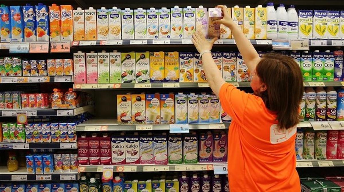 Una trabajadora ordena los productos en la estantería de un supermercado de Barcelona.