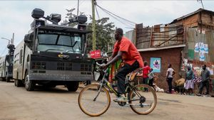 Un ciclista pasa por delante de un vehículo antidisturbios en las chabolas de Kibera, en Nairobi, el 7 de agosto.