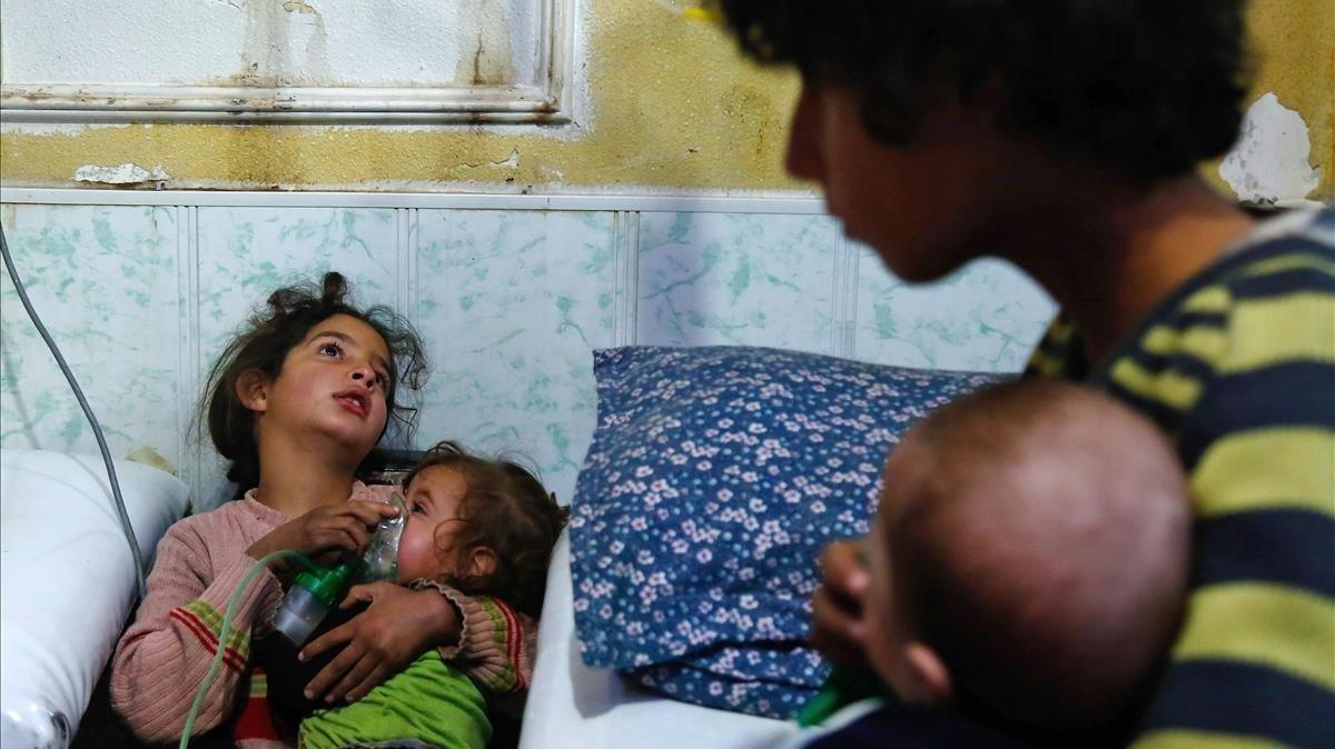 Una menorsiria sostiene la máscara de gas sobre el rostro una niña en un hospital de la localidad deDuma, en Siria, tras un ataque químico.