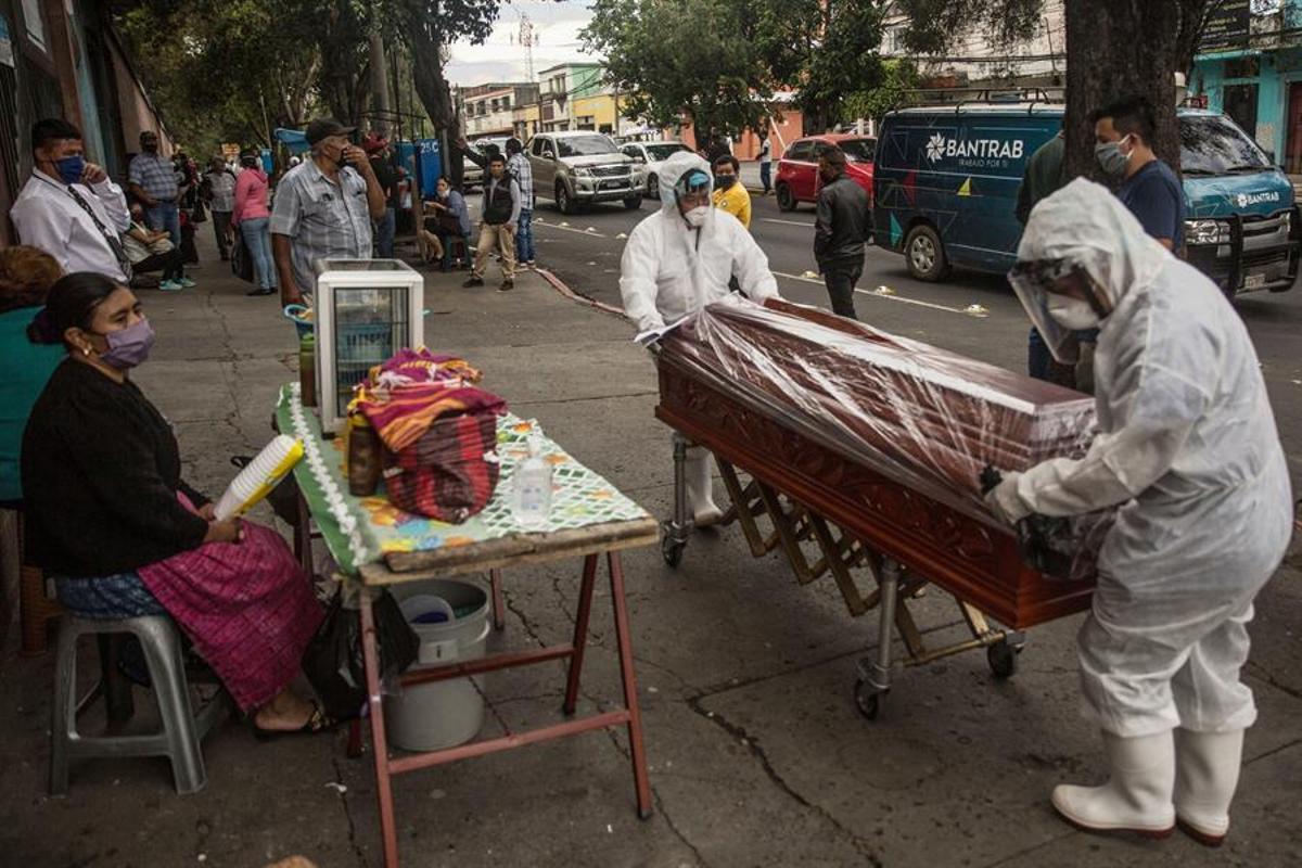Dos empleados funerarios trasladan hacia el cementerio La Verbena el féretro de una víctima de coronavirus, en el Hospital Nacional San Juan de Dios, en Ciudad de Guatemala.