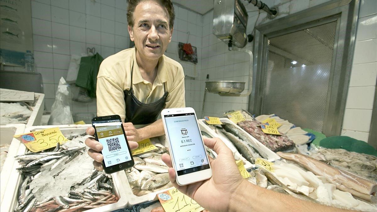 Un comerciante cobra a un cliente a través de la aplicación REC Barcelona.