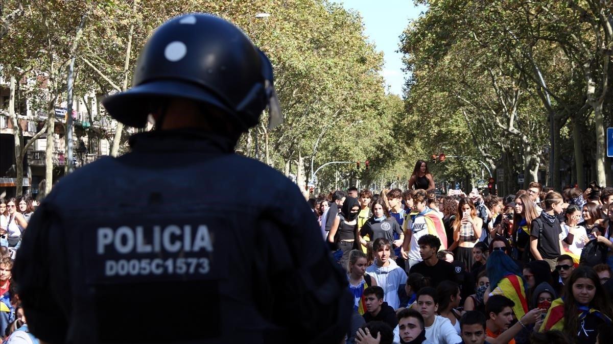 Un agente de policía, de espaldas, frente a unos manifestantes en la Gran Via de Barcelona, este miércoles.