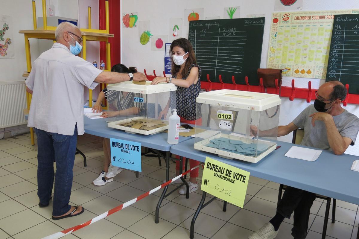 Un elector deposita su voto en un colegio electoral en Marsella, durante la segunda vuelta de las elecciones regionales francesas de este domingo.