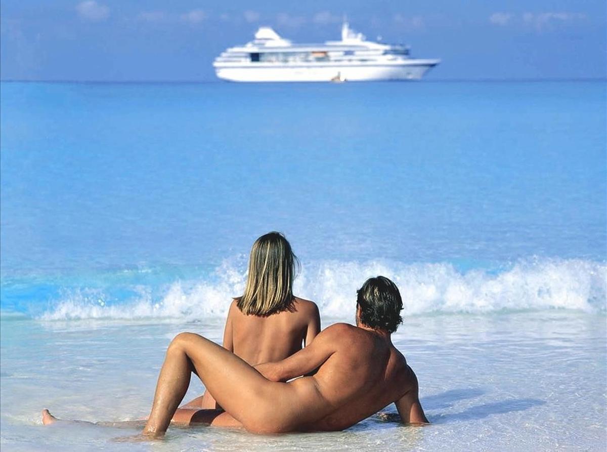Una pareja practica nudismo en una playa de un complejo de vacaciones de lujo.