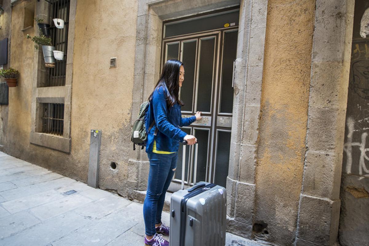 Una turista se dispone a entrar en el piso turístico alquilado.