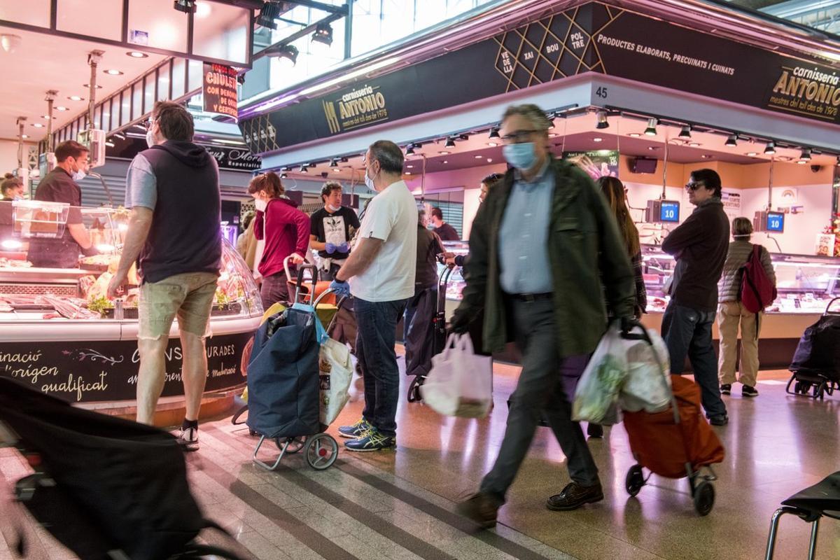 Clientes del mercado del Ninot de Barcelona mantienen su distancia de seguridad entre ellos.