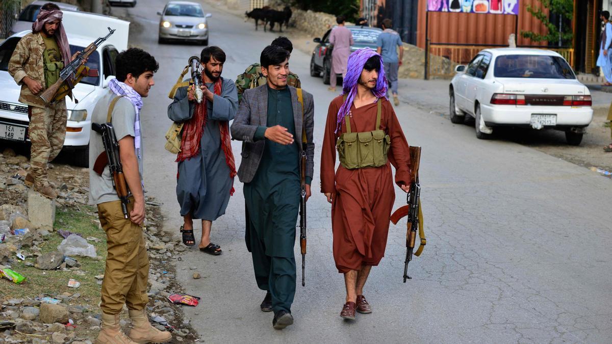 Hombres armados afganos, que apoyan a las fuerzas de seguridad afganas contra los talibanes, caminan por una carretera en Bazarak, provincia de Panjshir.