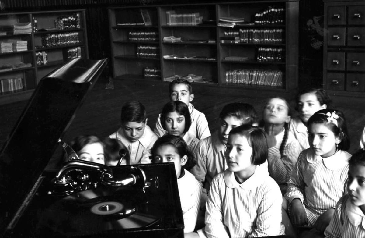 Estudiantes de la Escola del Mar escuchan música en una gramola.
