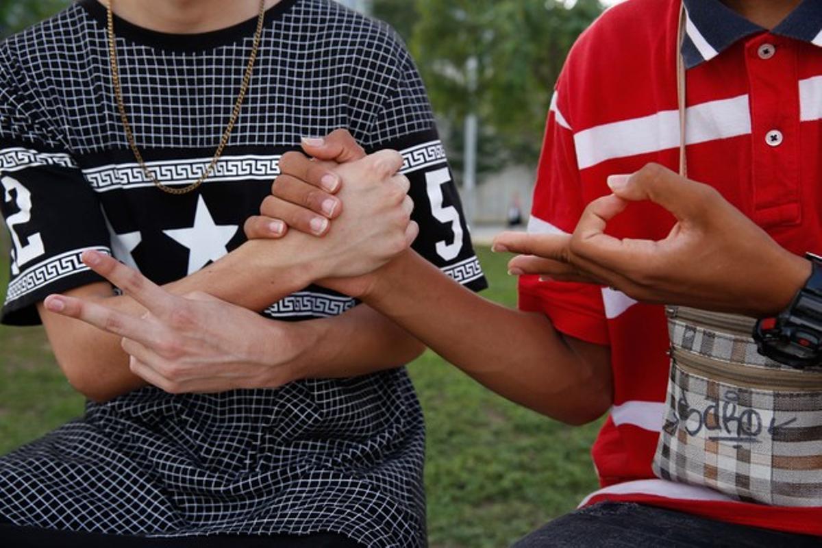 Dos jóvenes 'swaggers' se saludan en los alrededores del centro comercial Splau, en Cornellà, la semana pasada.