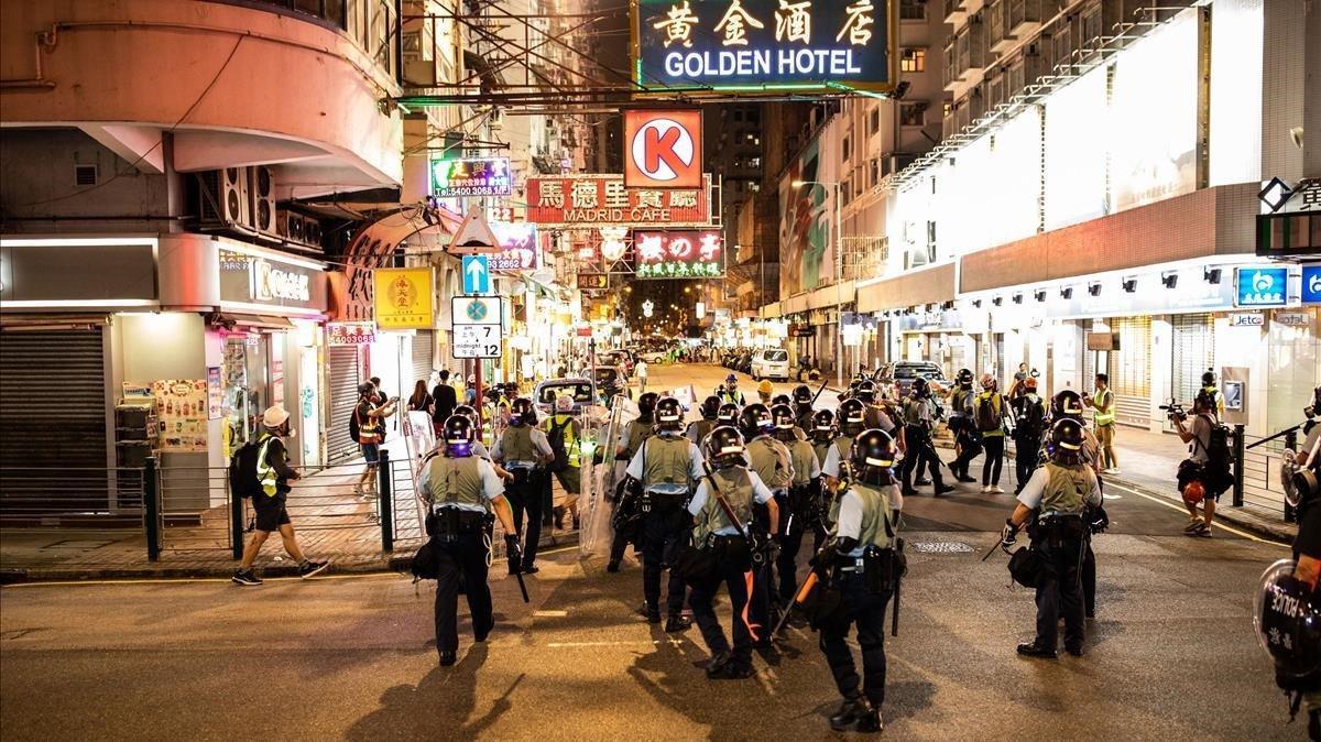 Un grupo de policías antidisturbios toma posición en una calle de Hong Kong.