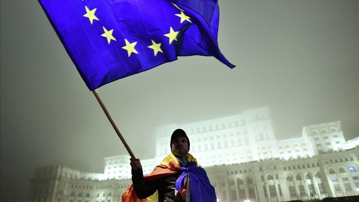 Un hombre enarbola la bandera europea frente al Parlamento rumano durante una protesta contra la corrupción, en noviembre del 2017 en Bucarest.