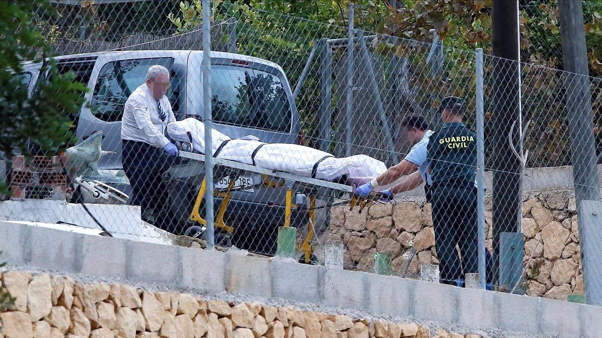 Miembros de los servicios funerarios trasladan el cuerpo de una de las víctimas que ha sido halladamuerta por arma de fuego en una vivienda del término municipal de Finestrat.