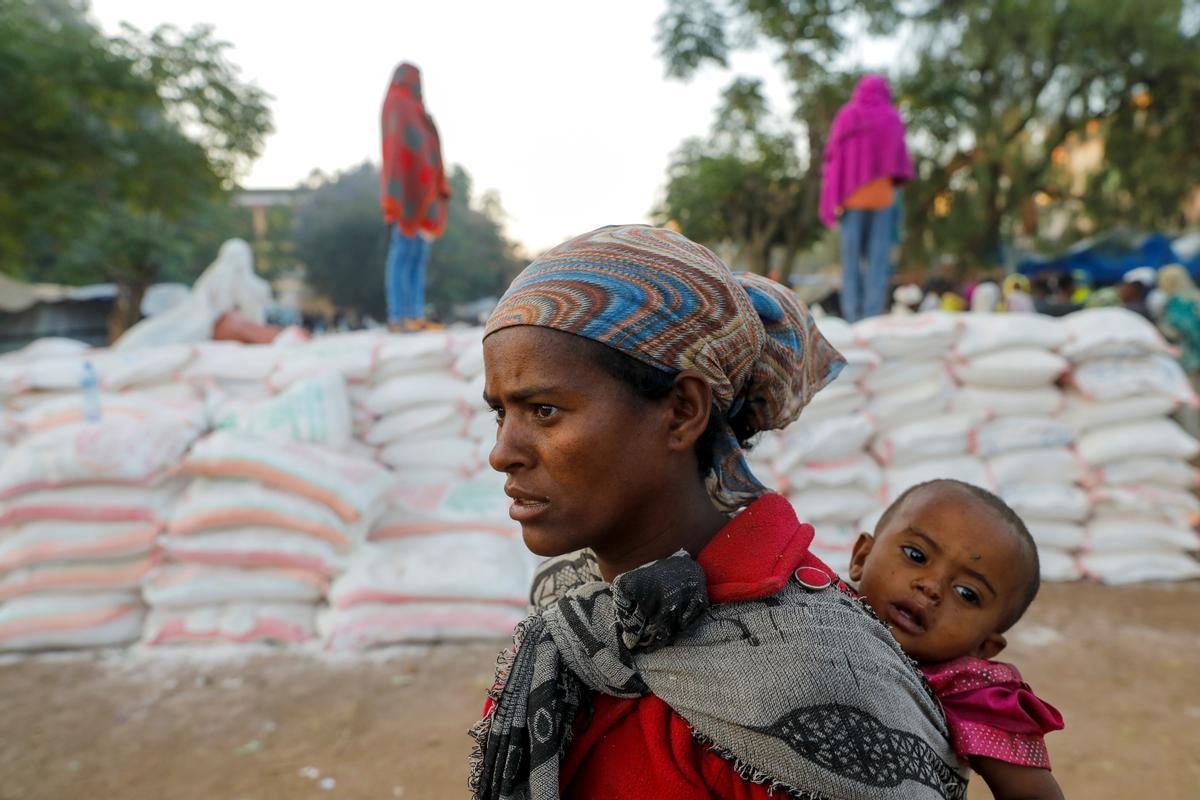 Una mujer carga a su hijo mientras hace cola para conseguir comida.