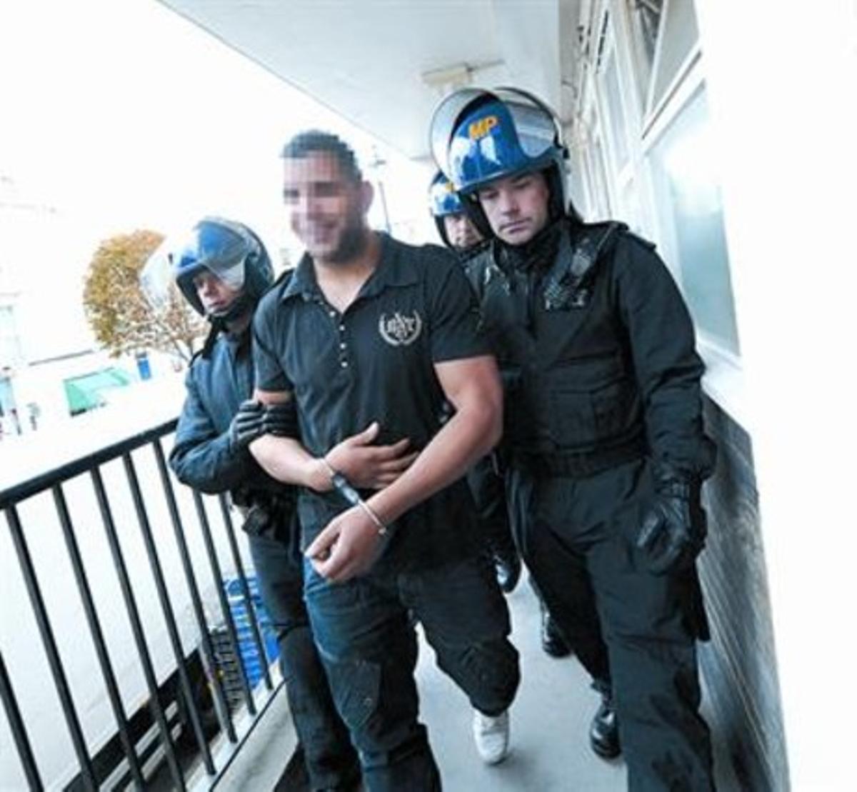 La policía se lleva a un hombre de su domicilio en Londres.