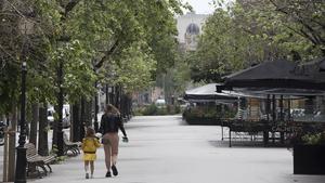 Una mujer camina con su hija por una Rambla de Catalunya desierta, el 23 de abril.