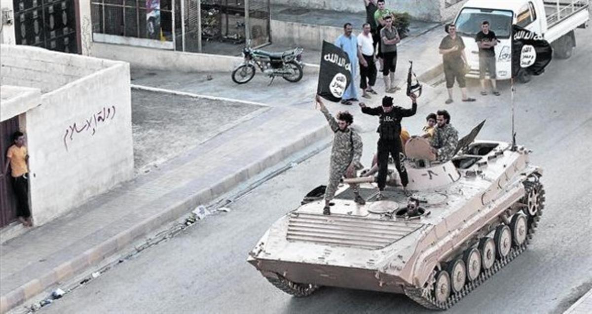 Yihadistas del Estado Islámico (EI) en un tanque por las calles de Raqqa.