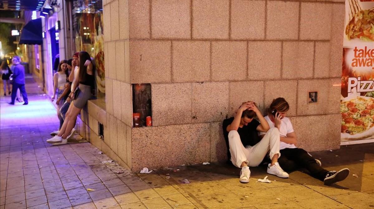 Jóvenes tirados en las cercanías de las discotecas del paseo Marítimo de la Barceloneta, la madrugada de este domingo.