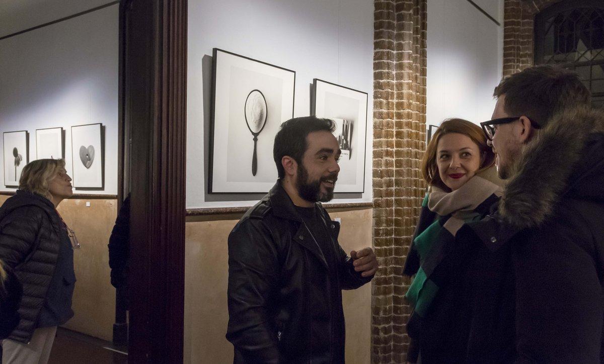 El autor (en el centro) conversa con unos visitantes de la exposición.