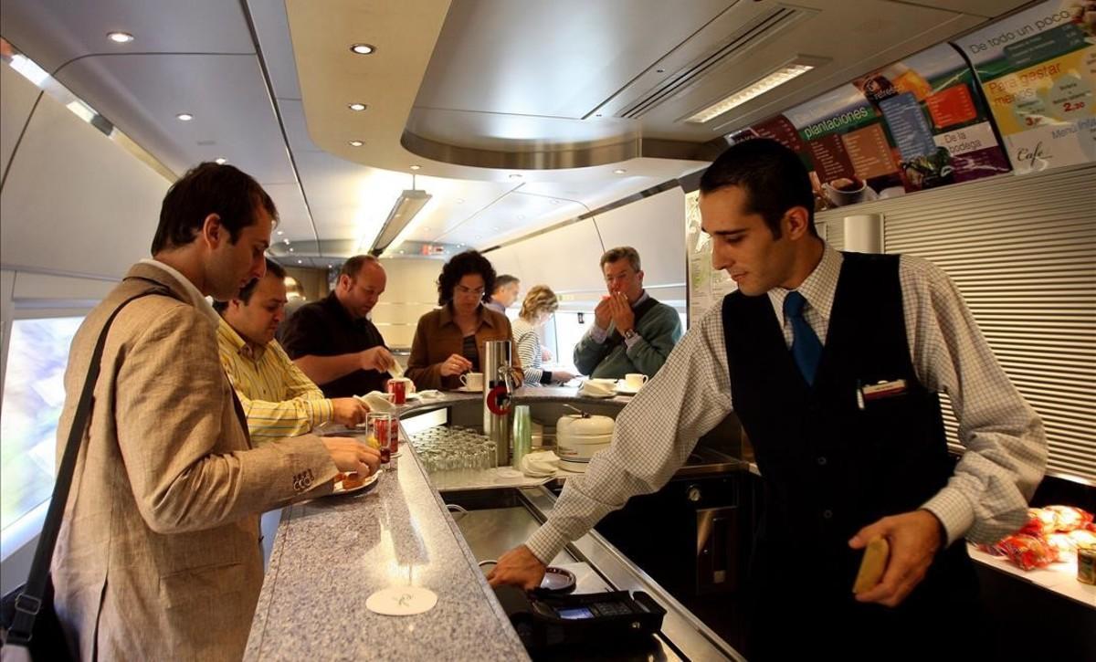 Un camarero sirve a un cliente en el bar de un tren AVE.