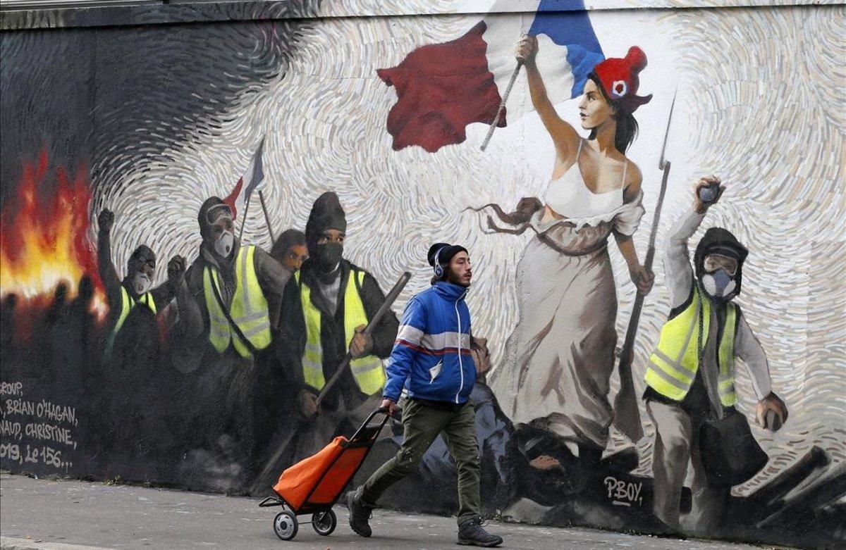 Un hombre pasa junto a un mural que reproduce una versión de 'La libertad guiando al pueblo', deEugene Delacroix, con la presencia de 'chalecos amarillos', idea del artista Pascal Boyart.