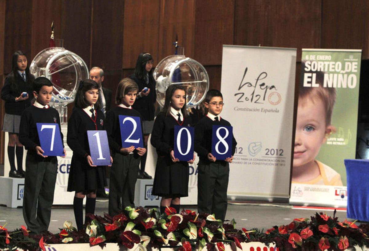 Los niños del Colegio de San Ildefonso sostienen el primer premio del sorteo de la lotería del Niño, el 71208.