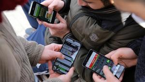 Un grupo de veinteañeros consulta aplicaciones de apuestas deportivas 'online' el 30 de diciembre