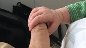 El recién nacido Ibai se agarra, con su robusta mano derecha, al dedo índice izquierdo de su abuelo Andoni Zubizarreta.