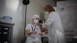 Una sanitaria inyecta una vacuna a una trabajadora del Hospital de la Santa Creu i Sant Pau de Barcelona.