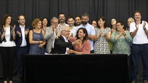 Ribó (Compromís) y Gómez (PSPV), con los concejales de ambas formaciones detrás, se felicitan tras firmar el acuerdo para gobernar València los próximos cuatro años