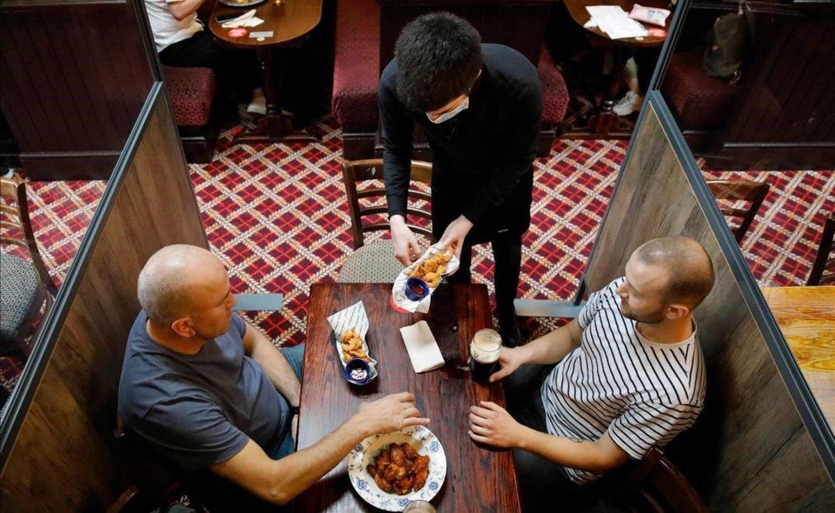 Un camarero protegido contra el covid sirve a los clientes en un pub de Londres.