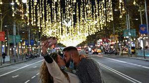 Una pareja se besa mientras se hace una selfie bajo la luz navideña en el paseo de Gràcia.