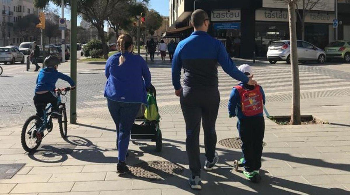 Unos padres pasean junto a sus tres hijos en una avenida de Palma de Mallorca.