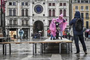 Unas niñas, sobre una de las pasarelas colocadas en previsión de inundaciones, el sábado en Venecia.