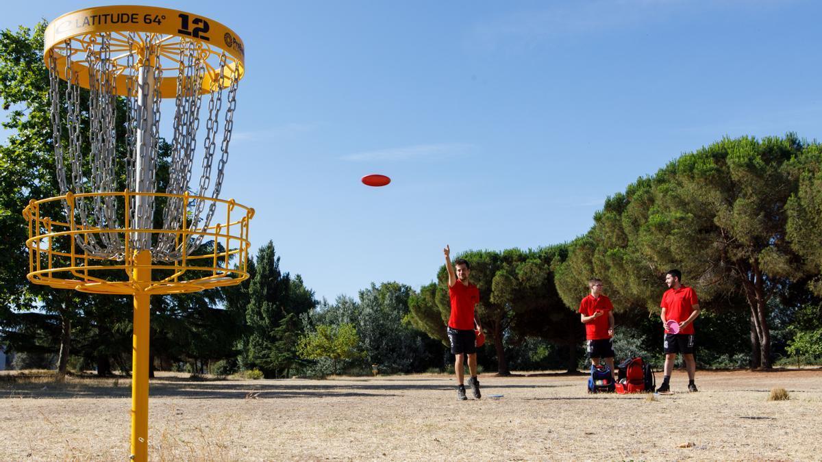 Merlin Sales-Tomas tira un frisbee a canasta junto a otros dos discgolfistas del club Flying Squirrels en el único campo oficial de Catalunya, en Palau-solità i Plegamans.
