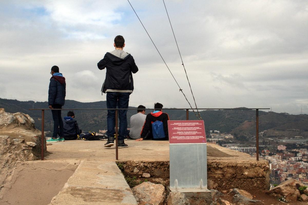Unosjóvenescontemplan las vistas deBarcelona desde una zona de acceso restringido de laantiguabatería del Carmel.