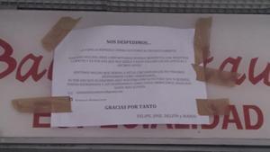 Nota de despedida pegada en la persiana del restaurante Romesco.