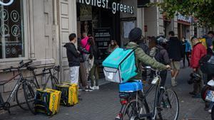 Varios 'riders' esperan ante un restaurante de Barcelona para recoger pedidos.