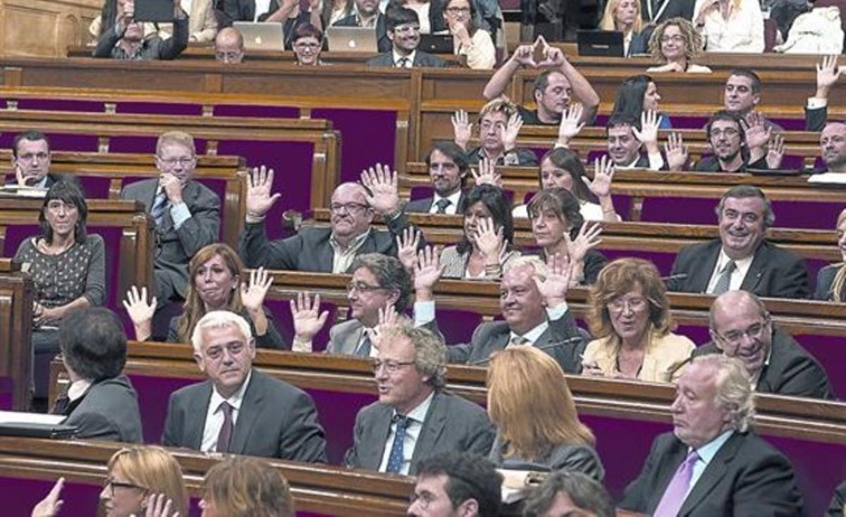 Los diputados del PP alzan las manos para mostrar que no pulsan ningún botón en la votación. Al fondo, Fernández (CUP) hace el símbolo feminista.
