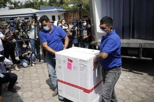 Dos hombres bajan de un camión una caja que contiene dosis de las vacunas contra el covid-19.