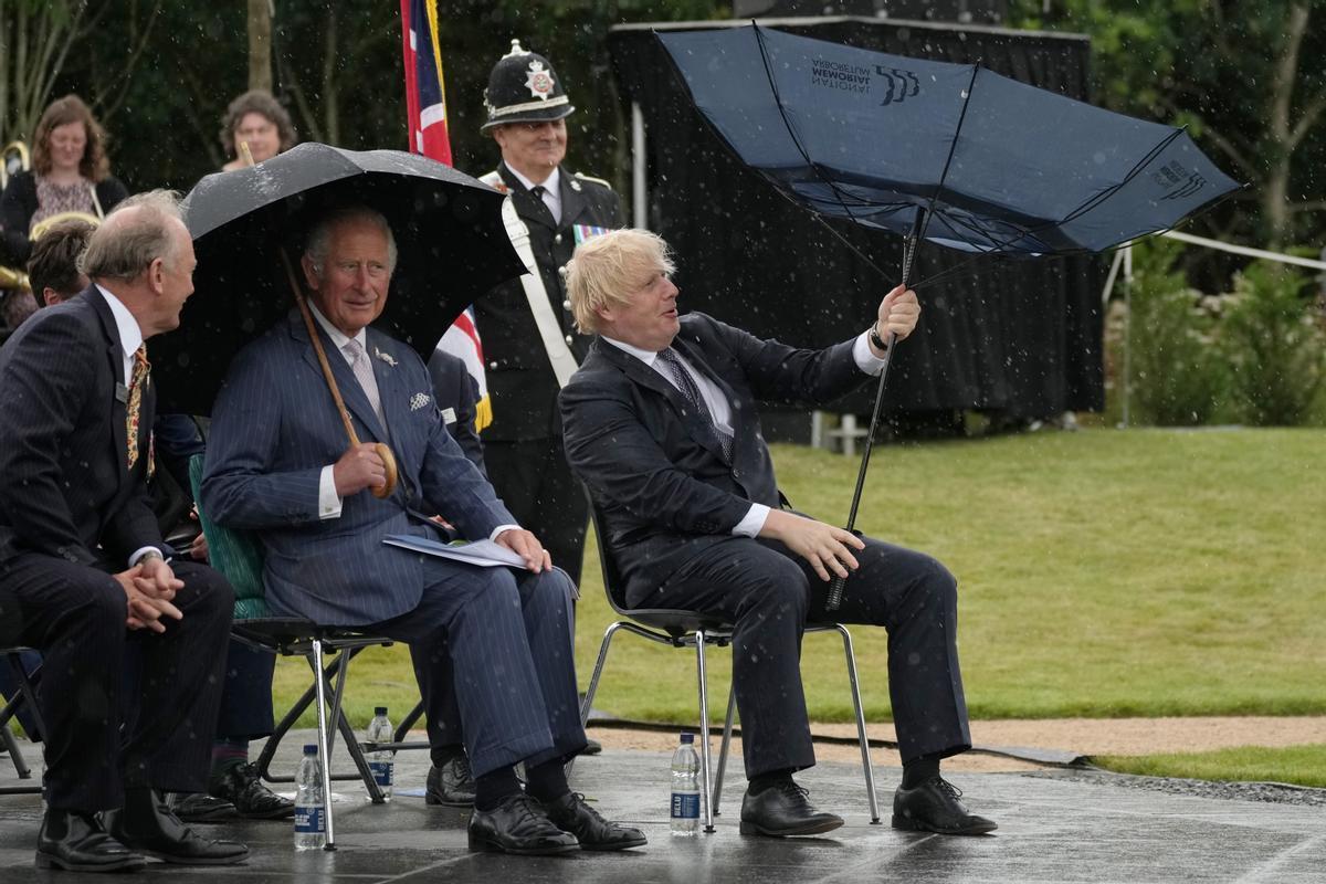 Boris Johnson trata de controlar el paraguas durante un acto oficial.