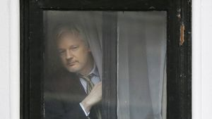 Julian Assange, detenido en la Embajada de Ecuador en Londres. En la foto, una imagen de archivo de Assange tras una de las ventanas del edificio.