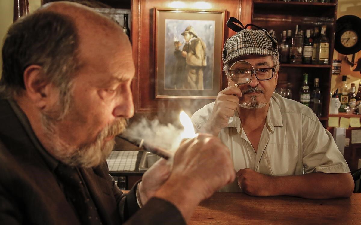 Ojeda (Harold Stackhurst), con gorra y lupa 'holmesianos' en el Pipa Club.